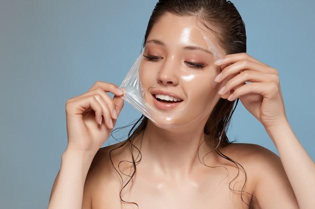 Молодая и красивая женщина снимает прозрачную маску с лица и улыбается