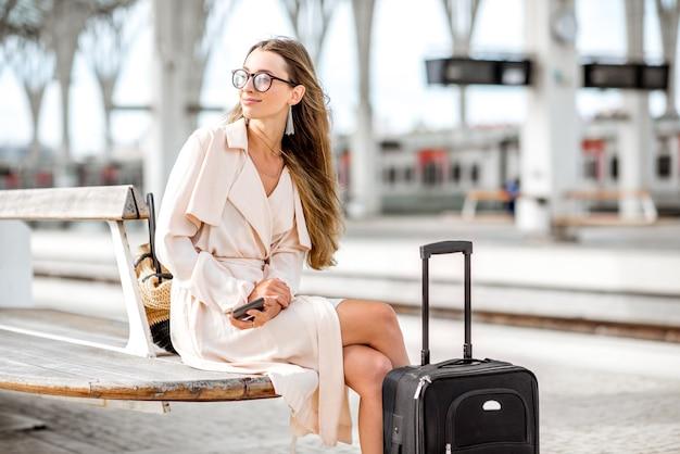 Молодая и красивая женщина сидит с багажом в ожидании поезда на вокзале