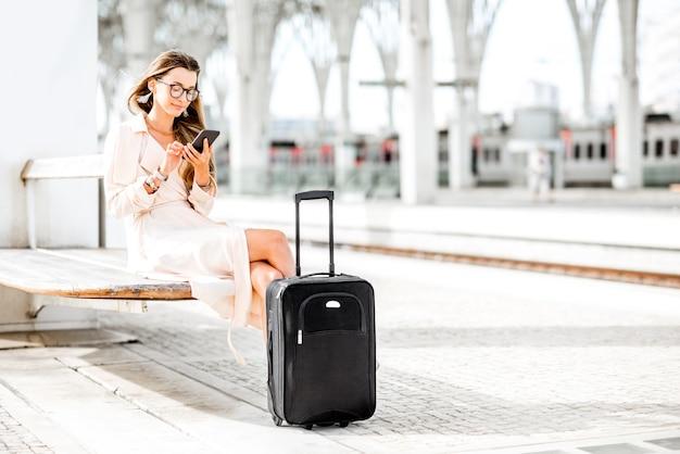 Молодая и красивая женщина по телефону ждет с багажом поезда на вокзале