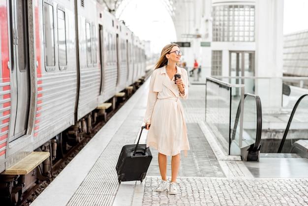Молодая и красивая женщина гуляет с чемоданом на современном вокзале возле поезда. концепция путешествия на поезде