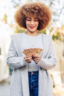 幸せな笑顔のアフロ髪の若くて美しい女性。街の通りにユーロ紙幣を持って笑顔で立っている