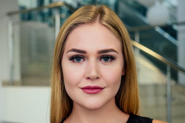 미용 스튜디오에서 인공 연장된 실크 속눈썹 눈을 가진 젊고 아름다운 여성이 완벽한 피부를 닫습니다