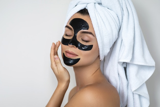 彼女の顔に黒の剥離マスクを持つ若くて美しい女性