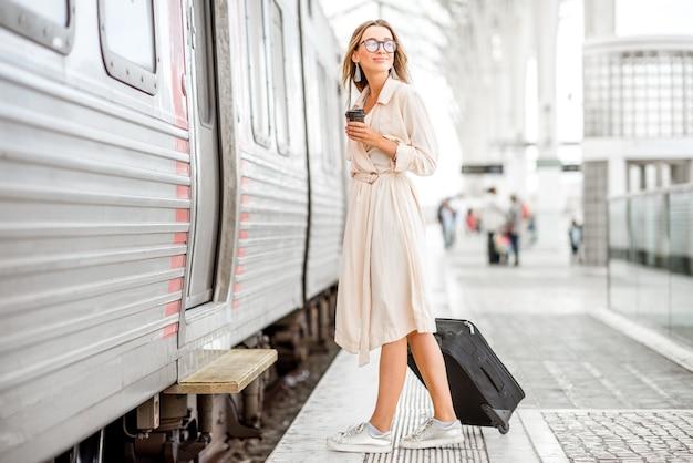 Молодая и красивая женщина с чашкой кофе и багажом, посадка в поезд на вокзале