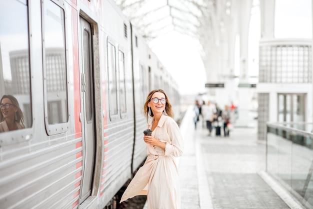Молодая и красивая женщина с чашкой кофе садится в поезд на современном железнодорожном вокзале