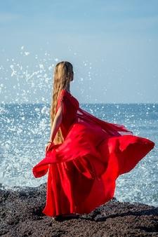 Молодая и красивая женщина с длинными волосами, стоящая в элегантном красном длинном шикарном роскошном платье на пляже с волнами. концепция шикарного отдыха на тропическом курорте