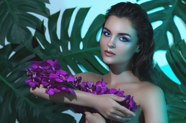 完璧な滑らかな肌を持つ若くて美しい女性は蘭の花を持っています。