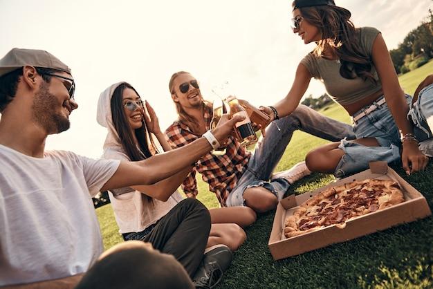 若くてのんき。屋外でピクニックを楽しみながらビール瓶で乾杯のカジュアルな服装で笑顔の人々のグループ