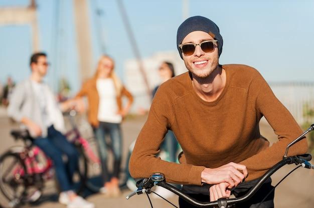 若くてのんき。彼の友人がバックグラウンドで話している間、彼の自転車に寄りかかって、笑顔でカメラを見ているハンサムな若い男