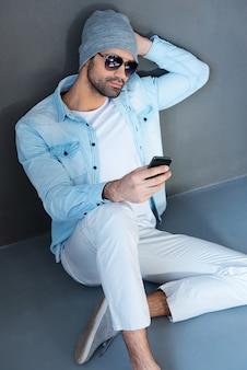 若くてのんき。灰色の背景に対して床に座っている間携帯電話を保持している眼鏡のハンサムな若い男の上面図