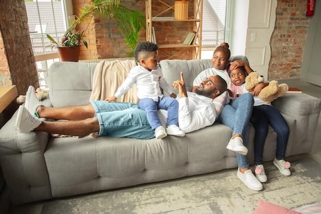 젊고 쾌활한 아프리카 가족이 집에서 함께 시간을 보내고 있습니다.