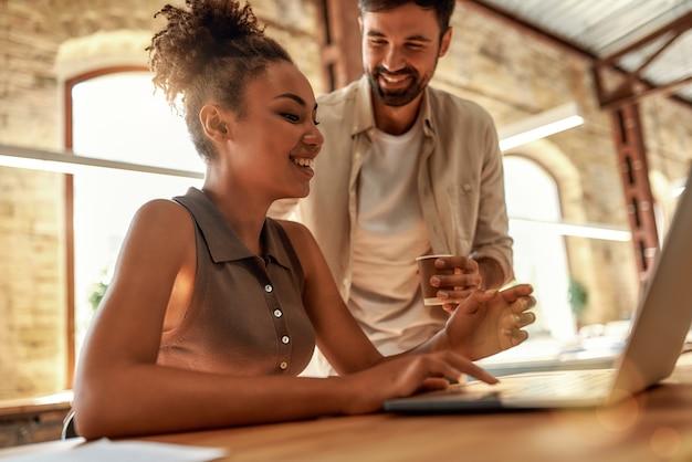 Молодой и веселый мужчина держит чашку кофе и разговаривает со своим коллегой во время совместной работы