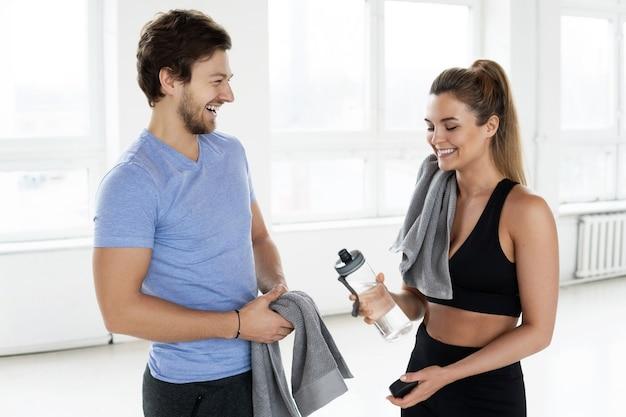 Молодые и веселые люди после тренировки в тренажерном зале. улыбающийся мужчина и женщина довольны результатом фитнес-тренировки.