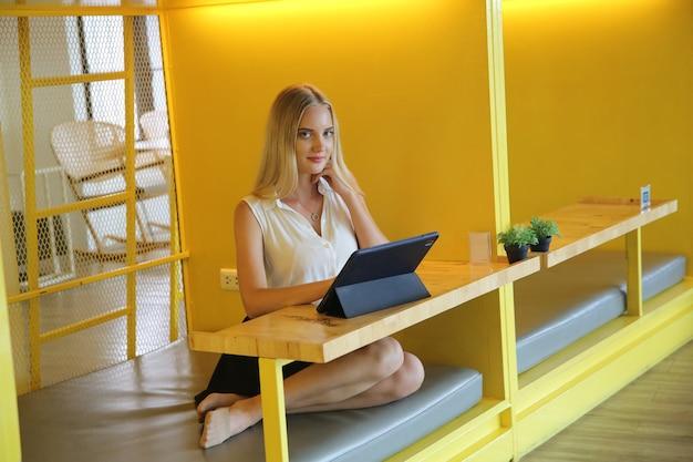 Молодая и жизнерадостная женщина, работающая над цифровым планшетом, используя беспроводной интернет, расслабленно сидя в кафе. понятие о досуге, фрилансе и мобильной работе