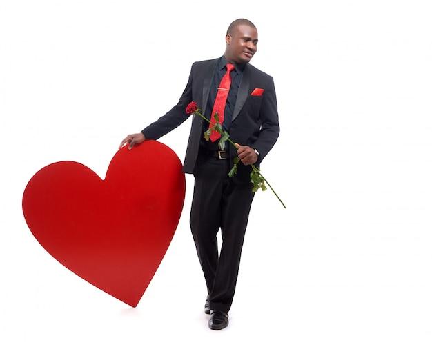 Молодой и уверенный африканский мужчина в люксе и красном галстуке держит красную розу