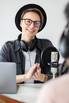 녹음실에서 팟캐스트를 녹음하는 젊고 자신감 있는 유럽 여성