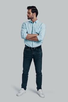 若くて自信がある。灰色の背景に立っている間、目をそらし、腕を組んでいるハンサムな若い男の全長
