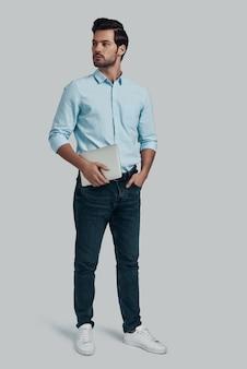若くて自信がある。灰色の背景に立っている間デジタルタブレットを運ぶ若い男の全長