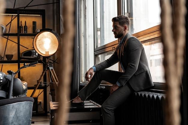 若くて自信がある。窓に座っているハンサムな若い男。