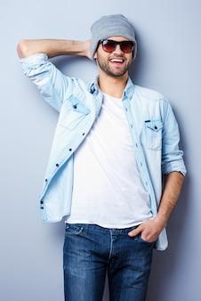 젊고 멋진. 선글라스와 모자를 쓰고 카메라를 보고 회색 배경에 서서 웃고 있는 잘생긴 젊은 남자