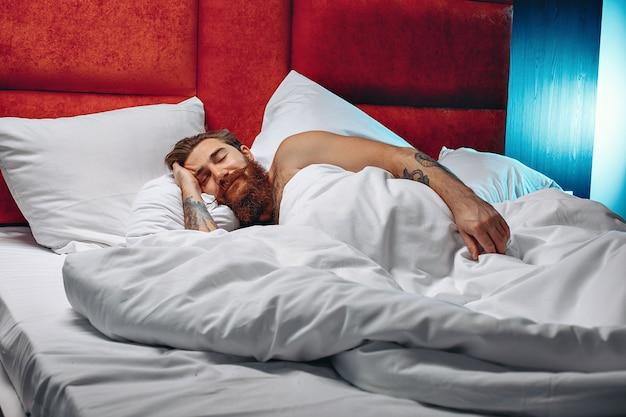 Молодой и смелый парень с длинными усами и бородой лежит на белой кровати и спит.