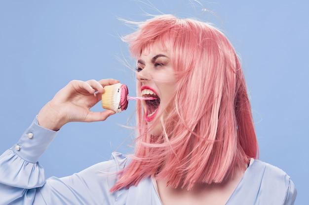 キャンドルでカップケーキを食べる若い、クレイジーな女性