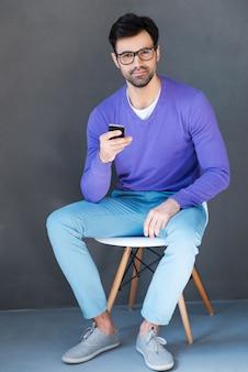 若くて創造的。携帯電話を保持し、灰色の背景に座ってカメラを見ているハンサムな若い男