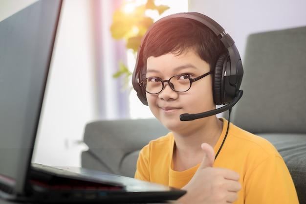 若くてかわいい10代の小さなアジア人の少年は、リビングルームに座ってヘッドフォンを着用し、ラップトップノートブックコンピューターを使用してオンライン距離学習を行い、コロナウイルスの発生時に幸せそうな顔で親指を立てます。