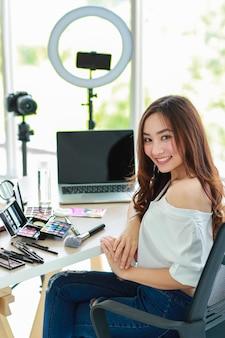 若くてかわいいアジアの女性のvlogger、インフルエンサー、または化粧品製品とデジタル一眼レフカメラとスマートフォンとラップトップノートブックコンピューターを持って座っているオンライン販売者は、ビデオライブストリームを放送する準備ができています。