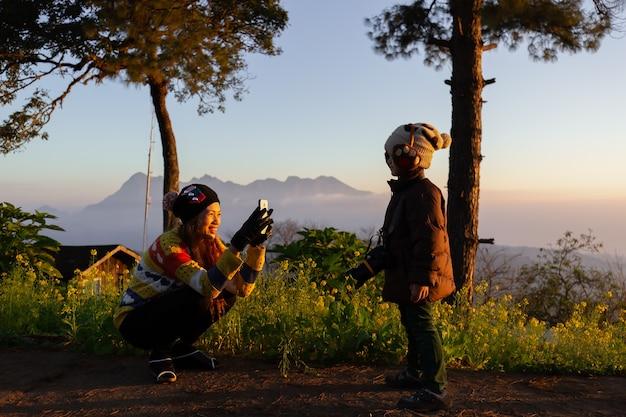Молодая и милая мама держит и с помощью смартфона фотографирует своего маленького сына в утреннем свете во время кемпинга и путешествия по высоким горам и лесам.
