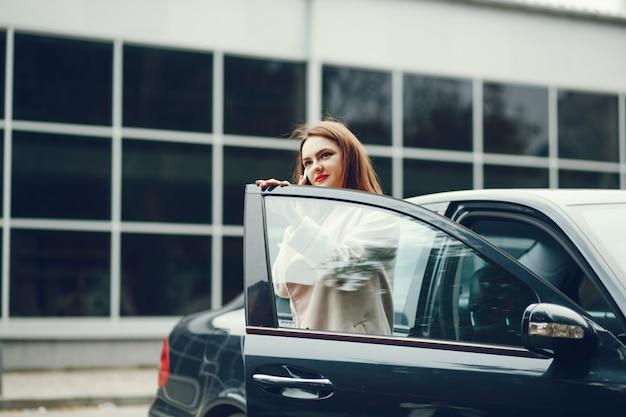 젊고 우아한 비즈니스 여자 차 근처에 서 전화를 사용하여