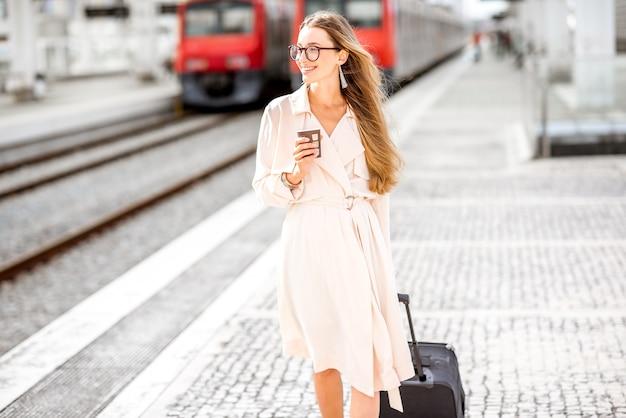 Молодая и элегантная бизнес-леди гуляет с чемоданом и чашкой кофе на платформе на вокзале