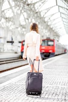 Молодая и элегантная женщина возвращается с багажом возле поезда на современном железнодорожном вокзале