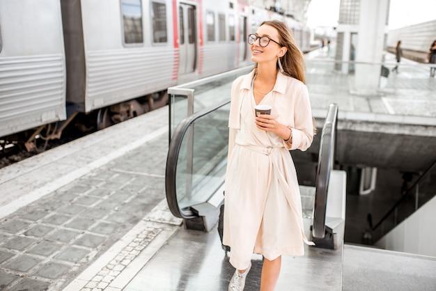 Молодая и элегантная женщина идет с багажом и чашкой кофе возле поезда на современном железнодорожном вокзале