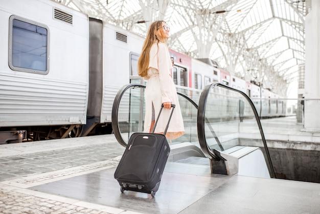Молодая и элегантная женщина гуляет с багажом возле поезда на современном железнодорожном вокзале