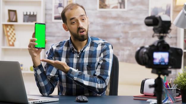젊고 유명한 인플루언서가 녹색 화면이 있는 전화기에 대한 리뷰를 촬영하고 있습니다. 크리에이티브 콘텐츠 크리에이터.