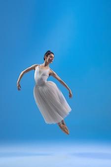 青い壁に分離された白いドレスの若くて優雅なバレリーナ