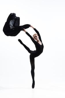 白いスタジオの背景に分離された最小限の黒のスタイルで若くて優雅なバレエダンサー。アート、モーション、アクション、柔軟性、インスピレーションのコンセプト。