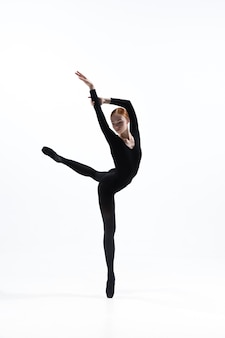 흰색 스튜디오 배경에 고립 된 최소한의 검은 스타일에 젊고 우아한 발레 댄서.