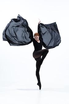 白いスタジオの背景に分離された最小限の黒のスタイルで若くて優雅なバレエダンサー。