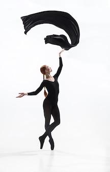 Молодой и изящный артист балета в минималистичном черном стиле, изолированные на белом фоне студии