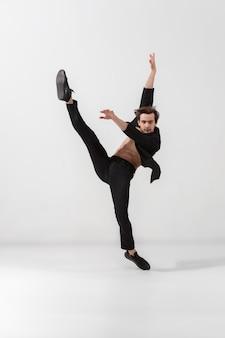 白いスタジオの背景に分離された最小限の黒のスタイルで若くて優雅なバレエダンサー