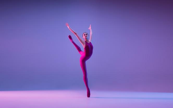 ネオンの光の中で紫色のスタジオの背景に分離された若くて優雅なバレエダンサー