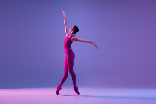 네온 불빛에 보라색 스튜디오 배경에 고립 된 젊고 우아한 발레 댄서