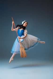 Молодая и изящная балерина в роли сказочного персонажа золушки на фоне студии