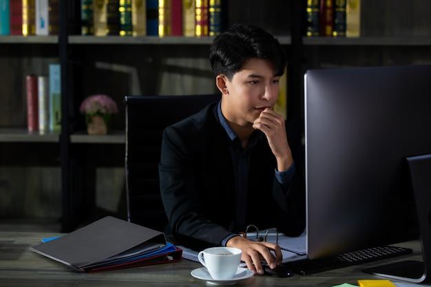 プライベートな作業室に座って、コンピューターの画面を見ているスーツを着た若くてハンサムなアジアのビジネスマン