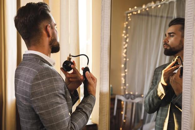 젊고 잘 생긴 수염 난 남자가 향수와 함께 분무기 노즐을 사용하고 있습니다.