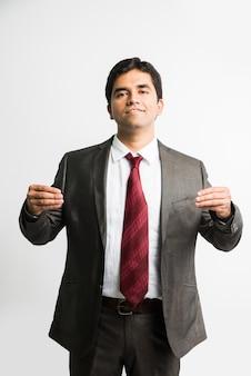 異なる言葉が白い背景の上に孤立して立っている白い色で切り絵によって書かれているバナーまたはボードを保持している若くてハンサムなインドのアジアのビジネスマン