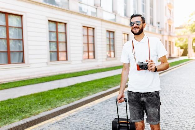 ひげを持つ若くてハンサムな男の観光客、スーツケースと彼の首にカメラを持って街を歩く