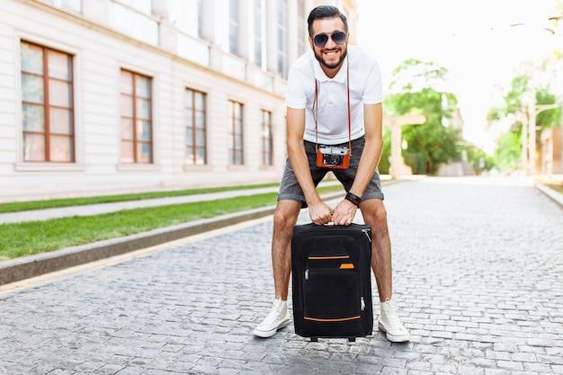 Молодой и красивый мужчина турист с бородой, гуляя по городу с чемоданом и камерой на шее